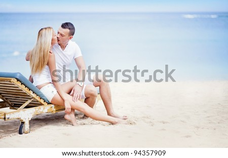 Young beautiful caucasian couple on the beach on sunbed