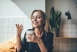 Young beautiful Caucasian happy smiling girl holding cup of hot coffee and smelling it during break in cafeteria, positive female enjoying aroma sniff of caffeine beverage feeling good in cafe