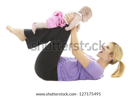 young beautiful caucasian mother holding her baby daughter doing baby yoga