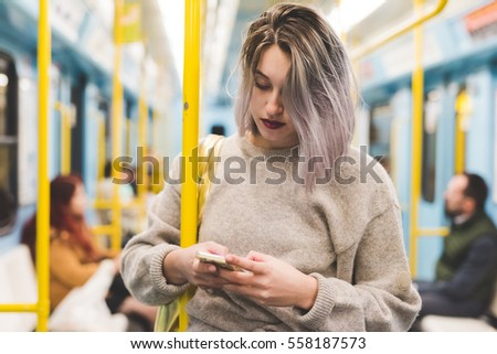 Shutterstock Young beautiful caucasian purple grey hair woman outdoor in the city on the subway using smart phone hand hold - technology, social network, communication concept