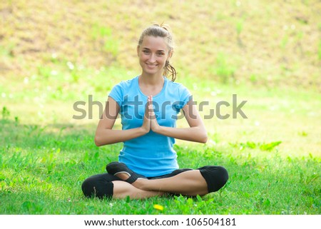 Young beautiful caucasian woman doing yoga meditation exercise on green grass at park