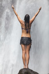 Young beautiful caucasian woman enjoying waterfall in the tropics