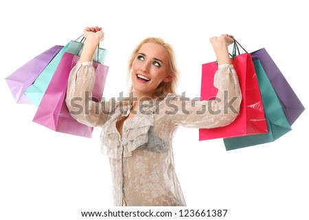 Young beautiful caucasian woman holds colorful shopping bags in her hands and smiling isolated over white background
