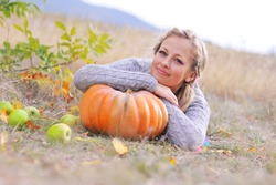 Young beautiful caucasian woman lying on the pumpkin outdoors