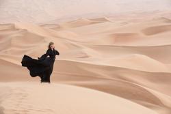 Young beautiful Caucasian woman posing in a traditional Emirati dress - abaya in Empty Quarter desert landscape. Abu Dhabi, UAE.