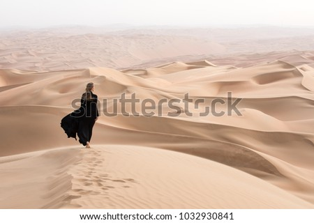 Young beautiful Caucasian woman posing in a traditional Emirati dress - abaya in Empty Quarter desert landscape. Abu Dhabi, UAE.