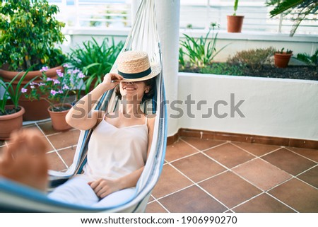 Young beautiful caucasian woman smiling happy resting on a hammock at home Photo stock ©