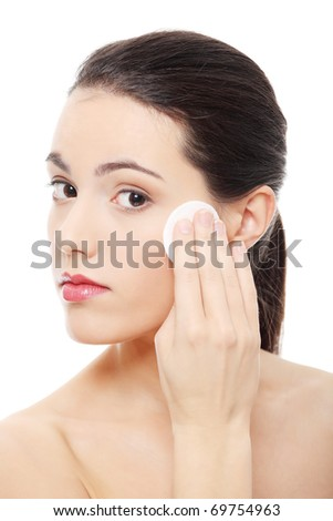 Young beautiful caucasian woman using a cotton pad to remove her make-up. Isolated on white