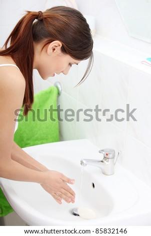 Young beautiful caucasian woman washing hands in bathroom.