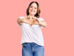 Young beautiful caucasian woman wearing casual white tshirt smiling in love doing heart symbol shape with hands. romantic concept.