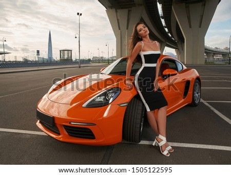 Young beautiful caucasian woman with long straight hair standing and posing near orange sport car at urban landscape. Outdoor fashion portrait