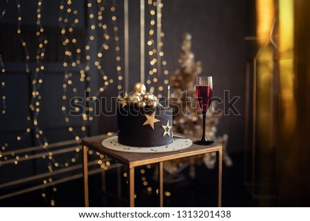 Young beautiful charismatic extraordinary girl woman in an elegant black dress in the image of the queen celebrates her birthday with a cake and candles, studio shooting, emotions, celebration, fun