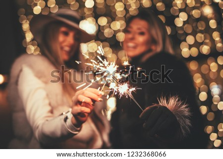Young beautiful cheerful female friends with sparklers having fun and enjoying in the city street at Christmas eve. Selective focus. Focus on foreground, on sparklers. #1232368066