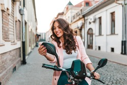 Young beautiful cheerful woman looking in mirror, while sitting on her scooter.