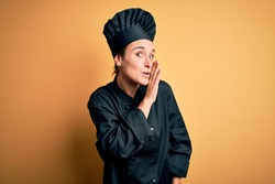 Young beautiful chef woman wearing cooker uniform and hat standing over yellow background hand on mouth telling secret rumor, whispering malicious talk conversation