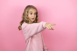 Young beautiful child girl standing over isolated pink background pointing with finger surprised ahead, open mouth amazed expression, something on the front