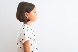 Young beautiful child girl wearing casual t-shirt standing over isolated white background looking to side, relax profile pose with natural face with confident smile.