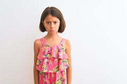 Young beautiful child girl wearing pink floral dress standing over isolated white background depressed and worry for distress, crying angry and afraid. Sad expression.