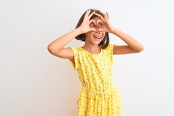 Young beautiful child girl wearing yellow floral dress standing over isolated white background Doing heart shape with hand and fingers smiling looking through sign