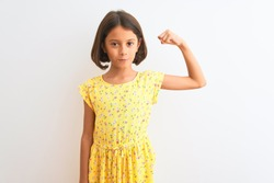 Young beautiful child girl wearing yellow floral dress standing over isolated white background Strong person showing arm muscle, confident and proud of power