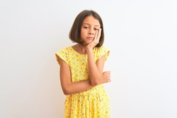 Young beautiful child girl wearing yellow floral dress standing over isolated white background thinking looking tired and bored with depression problems with crossed arms.