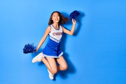 Young beautiful chinese girl smiling happy wearing cheerleader uniform. Jumping with smile on face using pompom over isolated blue background