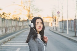 Young beautiful Chinese girl with headphones listening to music in the city streets