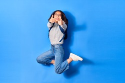 Young beautiful chinese student girl wearing glasses and backpack smiling happy. Jumping with smile on face doing ok sign with thumbs up over isolated blue background