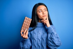 Young beautiful chinese woman holding chocolate bar over isolated blue background serious face thinking about question, very confused idea