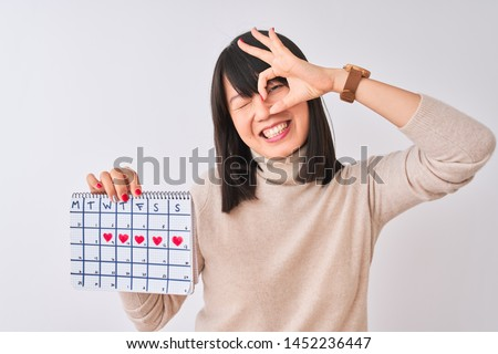 Young beautiful Chinese woman holding menstruation calendar over isolated white background with happy face smiling doing ok sign with hand on eye looking through fingers
