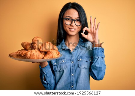 Young beautiful chinese woman holding plate with croissants over isolated yellow background doing ok sign with fingers, excellent symbol Stock fotó ©