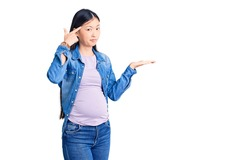 Young beautiful chinese woman pregnant expecting baby confused and annoyed with open palm showing copy space and pointing finger to forehead. think about it.