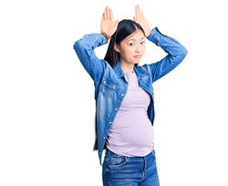 Young beautiful chinese woman pregnant expecting baby doing bunny ears gesture with hands palms looking cynical and skeptical. easter rabbit concept.