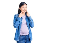 Young beautiful chinese woman pregnant expecting baby smiling with open mouth, fingers pointing and forcing cheerful smile