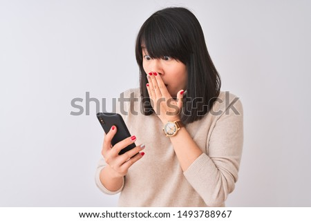 Young beautiful Chinese woman using smartphone standing over isolated white background cover mouth with hand shocked with shame for mistake, expression of fear, scared in silence, secret concept