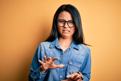 Young beautiful chinese woman wearing casual denim shirt over isolated yellow background disgusted expression, displeased and fearful doing disgust face because aversion reaction.
