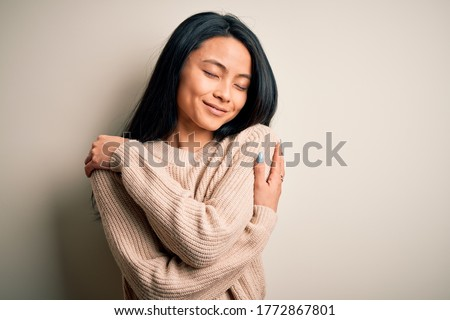 Young beautiful chinese woman wearing casual sweater over isolated white background Hugging oneself happy and positive, smiling confident. Self love and self care Сток-фото ©
