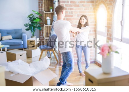 Young beautiful couple dancing at new home around cardboard boxes #1558610315