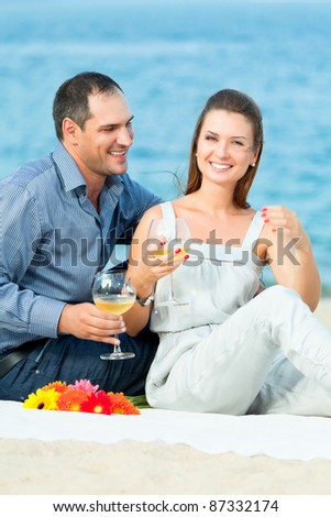 Young beautiful couple drinking wine on the beach