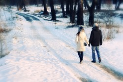 young beautiful couple having a walk in winter park