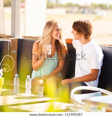 Young beautiful couple having fun in a beach bar