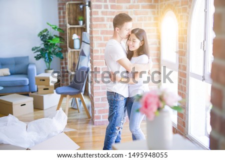 Young beautiful couple hugging at new home around cardboard boxes #1495948055