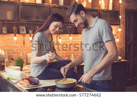 Young beautiful couple in kitchen. Family of two preparing food. Woman sitting on kitchen tabletop and helping man to make delicious pasta. Nice loft interior with light bulbs
