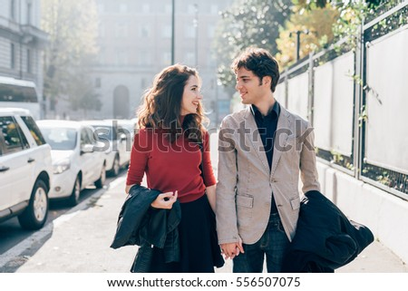 Young beautiful couple in love chatting walking outdoor in the city, having fun - first date,  romantic, love concept #556507075