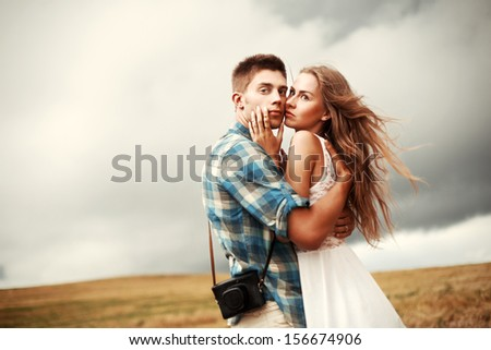 Young beautiful couple in love standing together in summer evening in countryside on the corn field. Handsome man posing with his blonde girlfriend.