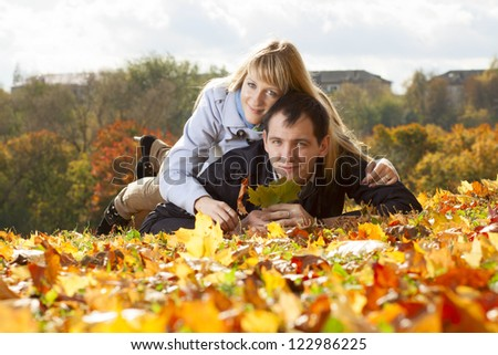 young beautiful couple is laying on the autumn foliage