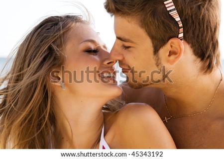 Young beautiful couple kissing at the sea shore