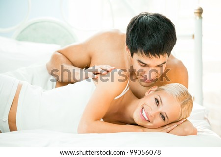 Young beautiful couple making love in bed
