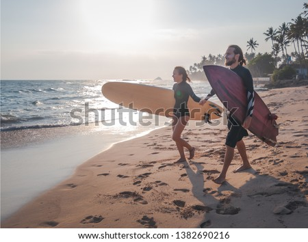 Young beautiful couple of friends on the ocean with surfboards in their hands, sports, active lifestyle, vacation, honeymoon #1382690216