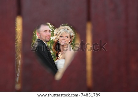 young beautiful couple outdoors viewed through heart-shaped hole in fence